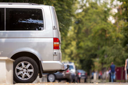 Side view detail of white passenger medium size luxury minibus van parked on summer city street pavement with blurred silhouettes of pedestrians on green trees bokeh copy space background.