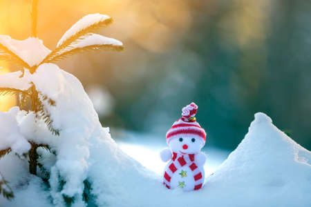 Small funny toy baby snowman in knitted hat and scarf in deep snow outdoors on bright blue and white copy space background. Happy New Year and Merry Christmas greeting card. Stock Photo