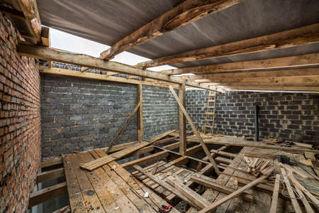 Spacious attic room under construction and renovation. Energy saving walls of large hollow foam insulation blocks and temporary wooden scaffolding, long logs as roof frame. Construction, masonry.