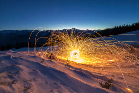 Light painting art. Spinning steel wool in abstract circle, firework showers of bright yellow glowing sparkles on winter snowy valley on mountain ridge and blue night starry sky copy space background. Stock Photo