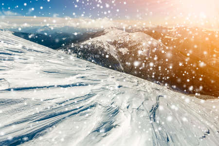 Beautiful winter landscape. Steep mountain hill slope with white deep snow, distant mountain range panorama, large snowflakes and bright shining sun rays on blue sky colorful copy space background.