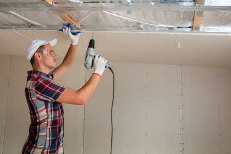Young man in goggles fixing drywall suspended ceiling to metal frame using electrical screwdriver on ceiling insulated with shiny aluminum foil. Renovation, construction, do it yourself concept. Stock Photo
