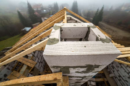 Top view of roof frame of rough wooden lumber beams and planks on walls made of hollow foam insulation blocks on rural landscape background. Building, roofing, construction and renovation concept.
