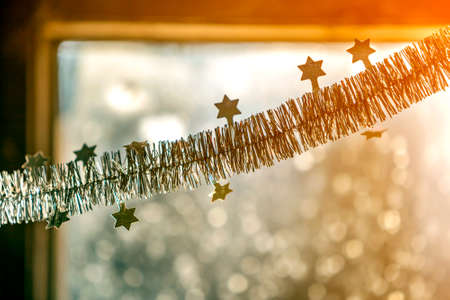 Close-up detail new year Christmas decoration, silver stars and rain on window light blurred bokeh background. Sparkling DIY decoration ideas for New Years Eve celebration party.
