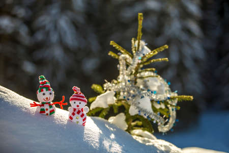 Two small funny toys baby snowman in knitted hats and scarves in deep snow outdoors near pine tree branch. Happy New Year and Merry Christmas greeting card.