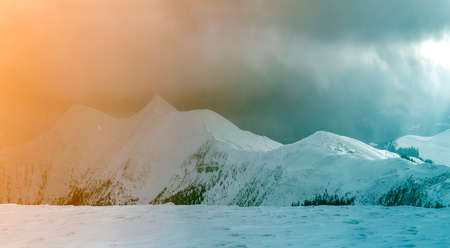 Winter mountain view in Carpathian mountains with dramatic clouds.