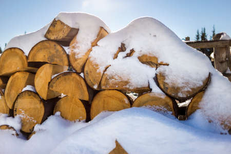 Neatly piled stack of chopped dry trunks wood covered with snow outdoors on bright cold winter sunny day, abstract background, Fire wood logs prepared for winter, ready for burning. Stock Photo