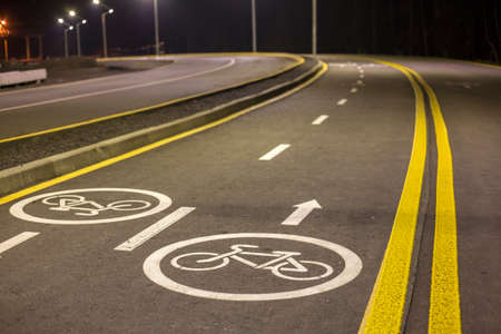 Bicycle Road Markings and Signs. Illuminated bicycle lane travel lane reserved for bicyclists with pavement markings with arrows that direct bicyclists in the direction of travel at night. Stock Photo