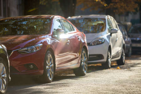 Long row of different shiny cars and vans parked along empty roadside on sunny autumn day on blurred green golden foliage bokeh background. Modern city lifestyle, vehicles parking problem concept.