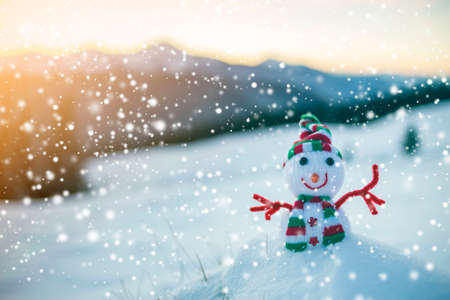 Small funny toy baby snowman in knitted hat and scarf in deep snow outdoor on blurred mountains landscape and falling big snowflakes background. Happy New Year and Merry Christmas greeting card theme. Stock Photo