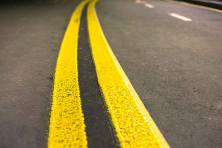 Wide bright yellow street marking sign line along modern wide smooth empty asphalt highway stretching to horizon. Speed, safety, comfortable journey and professional road building concept.