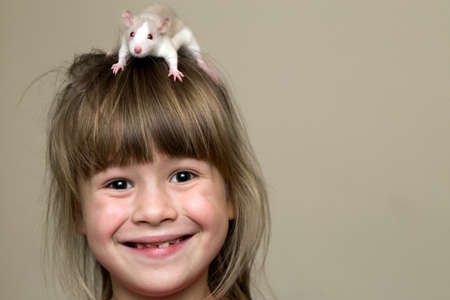 Portrait of happy smiling funny cute child girl with white pet mouse hamster on head on light wall copy space background. Keeping pets at home, care and love to animals concept. Stock Photo