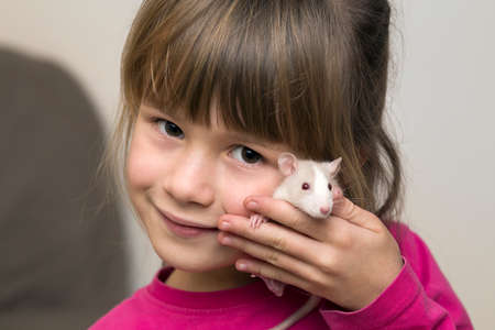 Portrait of happy smiling cute child girl with white pet mouse hamster on light copy space background. Keeping pets at home, care and love to animals concept. Stock Photo