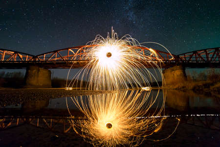 Light painting art concept. Spinning steel wool in abstract circle, firework showers of bright yellow glowing sparkles on long bridge reflected in river water on blue night starry sky background.