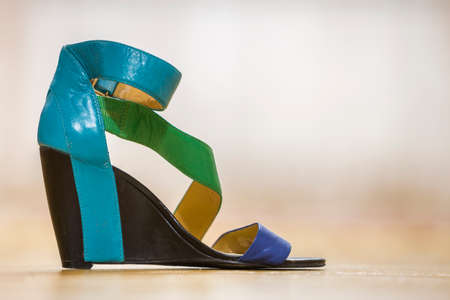 One colorful bright blue, green and yellow leather strap female shoe sandal on high black platform isolated on light copy space background. Style and fashion, modern comfortable footwear for summer. 스톡 콘텐츠