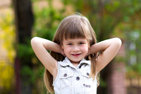 Portrait of a pretty little long-haired blond preschool girl in sleeveless white dress smiling shyly into camera against blurred outdoors background. Innocent happy childhood concept. Stock Photo