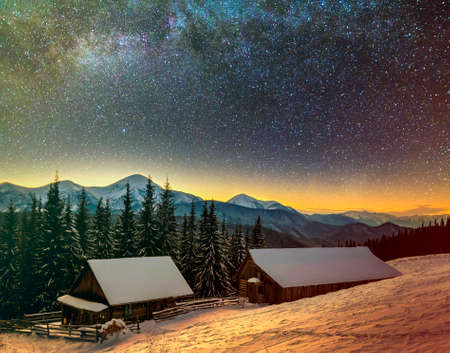 Old wooden house, hut and barn, pile of firewood in deep snow on mountain valley, spruce forest, woody hills on dark starry sky and Milky Way copy space background. Mountain winter night landscape. Фото со стока