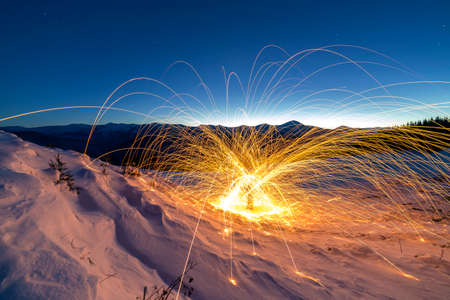Light painting art. Spinning steel wool in abstract circle, firework showers of bright yellow glowing sparkles on winter snowy valley on mountain ridge and blue night starry sky copy space background. Reklamní fotografie