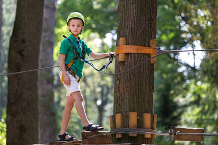 Young child boy in safety harness and helmet attached with carbine to cable moves confidently along rope way in recreation park on green foliage sunny bokeh background. Sport, game, leisure concept.