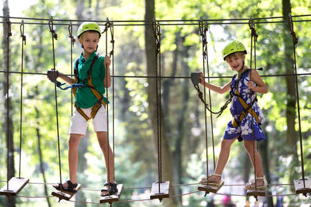 Two cute happy young children, boy and girl in protective harness, carbine and safety helmets on rope way on bright sunny day on green foliage bokeh background. Outdoors activities, games concept.