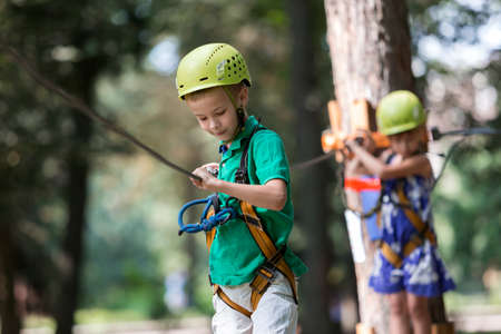 Young cute blond smiling child boy in safety harness and helmet attached with carbine to cable moves along rope way on bright sunny bokeh background. Sport, game, leisure, outdoor activity concept. Reklamní fotografie