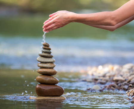 Close-up abstract image of woman hand pouring water on rough natural brown uneven different sizes and form stones balanced like pyramid pile landmark on blurred blue-green copy space background.