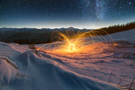Light painting art. Spinning steel wool in abstract circle, firework of bright yellow glowing sparkles on snowy white valley on woody mountain ridge and blue night starry sky copy space background.