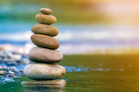Imagen abstracta de primer plano de diferentes tamaños y formas desiguales marrón natural áspero mojado y piedras de formas equilibradas como hito de pila de pirámide en aguas poco profundas sobre fondo de espacio de copia brumosa azul-verde borrosa. Foto de archivo