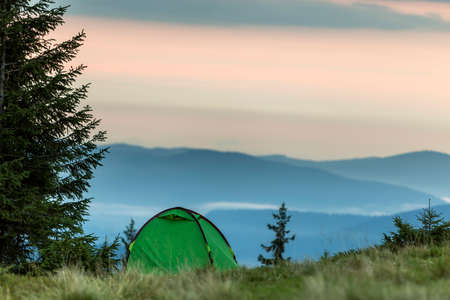 Tourist tent on grassy hill on distant misty blue mountains and clear pink sky before sunrise or sunset background. Summer camping in mountains at dawn. Tourism, hiking and beauty of nature concept.