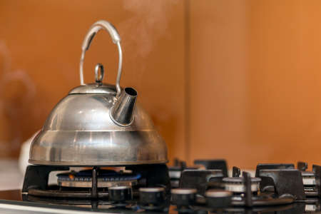 Shiny stainless tea kettle teapot with boiling water on gas stove on kitchen yellow copy space background. Stockfoto