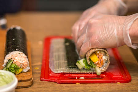 Process of making sushi and rolls. Close-up of man chef hands preparing traditional Japanese food at home or in restaurant on kitchen table. 免版税图像