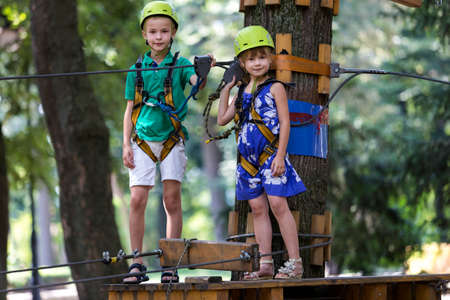 Two cute happy young children, boy and girl in protective harness, carbine and safety helmets on rope way on bright sunny day on blurred green trees background. Outdoors activities, games concept. Reklamní fotografie