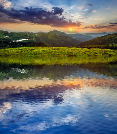 Mountain view at sunset. Panorama of green grassy valley, woody foggy mountains peaks with snow patches, dramatic cloudy sky and setting on horizon bright sun reflected in clear lake water.
