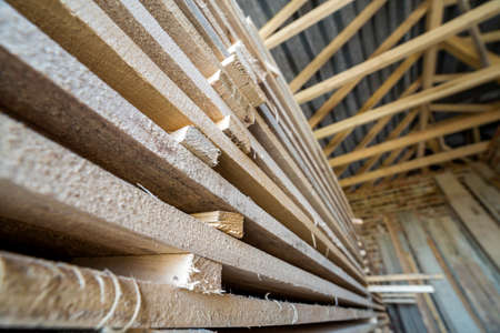 Perspective view of neatly piled long stack of natural uneven rough wooden boards inside attic room under construction. Industrial timber for carpentry, building, lumber material for construction. 版權商用圖片