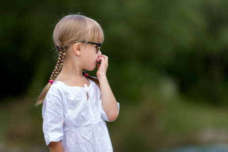 Portrait of cute pretty funny fashionable moody unsatisfied upset angry young girl with blond braids in white dress and dark sunglasses on blurred sunny summer green outdoors copy space background. Foto de archivo
