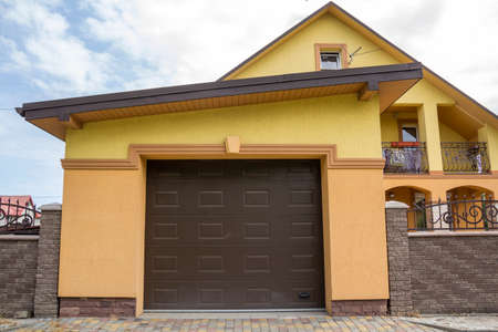View from the clean paved street of detached garage with big automatic door, new residential cottage with balcony behind brown brick forged fence. Real estate property and prosperity concept.