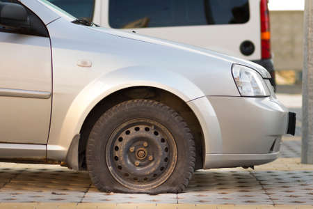 Flat tire of car on pavement. Side view outdoors of vehicle close up. Transportation problem, accident and insurance concept. Banque d'images