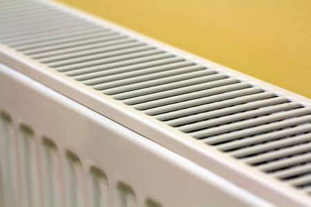 Close-up of white heating radiator detail on light yellow wall copy space background. Comfortable warm home interior, climate control concept.