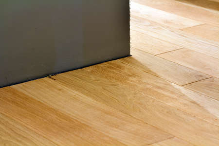 Natural light brown wooden parquet floor boards. Sunny soft yellow texture, copy space perspective background.