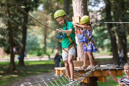 Two young children, boy and girl in protective equipment and safety helmets at climbing activity on rope way on bright sunny day on blurred green trees background. Outdoors activities, games concept. Reklamní fotografie