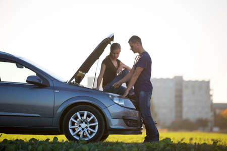 Handsome man at car with popped hood checking oil level in engine using dipstick and attractive woman watching on clear sky background. Transportation, vehicles problems and breakdowns concept.