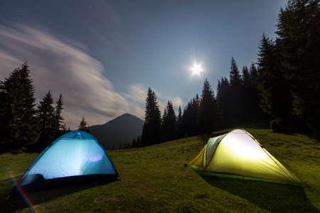 Grande luna luminosa in cielo nuvoloso blu scuro sopra due tende turistiche sulla radura erbosa verde della foresta fra i pini alti sul fondo distante della montagna. Turismo, campeggio notturno in montagna d'estate.