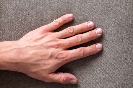 Close-up of male masculine hand with rough skin and short fingernails resting on flat copy space background, top view. Manual labor and hands care concept.