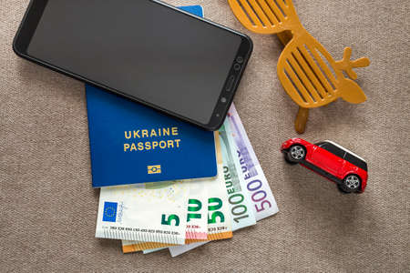 Black cellphone, Euro money banknotes bills, passport, toy car and funny sunglasses on copy space background, top view. Travel light, comfortable journey vacation planning concept. Reklamní fotografie