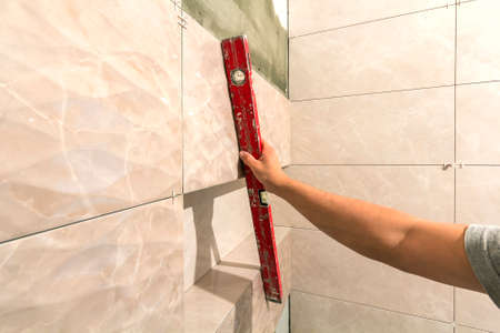 Close-up of worker tiler hand with lever installing on walls ceramic tiles. Tiles installation, tools and home improvement, renovation and construction, comfortable modern home concept. Stockfoto