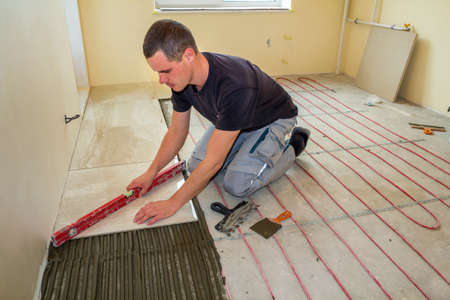 Young worker tiler installing ceramic tiles using lever on cement floor with heating red electrical cable wire system. Home improvement, renovation and construction, comfortable warm home concept. 版權商用圖片 - 117593538