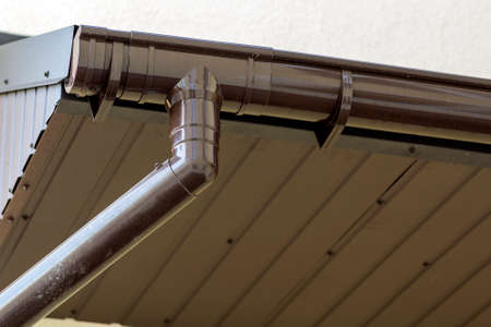 Close-up detail of cottage house corner with brown metal planks siding and roof with steel gutter rain system. Roofing, construction, drainage pipes installation and connection concept.