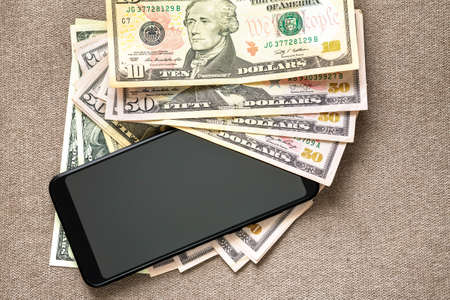 New black modern cellphone on money dollars banknotes background. Modern technology, communication and online trade using gadget concept.