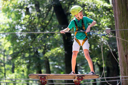 Young cute child boy in summer clothing, safety harness and helmet attached with carbine to cable moves slowly along rope way on green trees sunny bokeh background. Sport, game, leisure concept. Standard-Bild