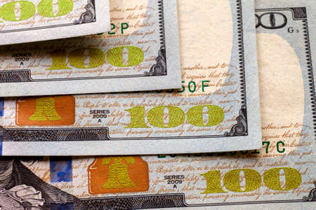 Money, prosperity and finances concept. Abstract light background of American USA national currency banknotes, details of neatly stacked bills worth one hundred dollars.